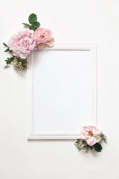 White blank wooden picture frame mockup. Wedding sign board still life composition with floral decoration of peony, eucalyptus and rose flowers isolated on white byckground. Flat lay, top view.