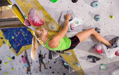 Female practicing indoor rock-climbing