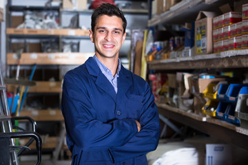 Portrait of happy male in uniform on his workplace in building store.