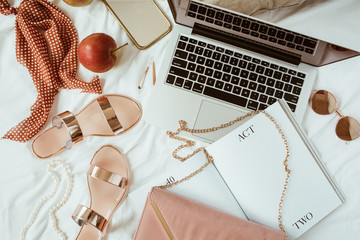 Women fashion pink styled home work space with bijouterie on white linen. Laptop, slippers, purse bag, sunglasses, jewelry. Flat lay, top view girl boss business hero header concept.