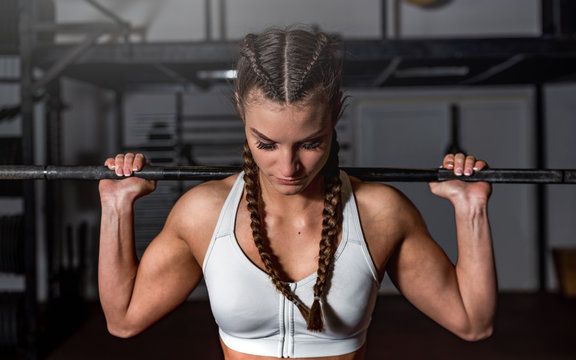 Young sweaty strong muscular fit girl with big muscles holding barbell behind her head preparing and concentrating for hard squats crossfit workout training with heavy weights in the gym close up
