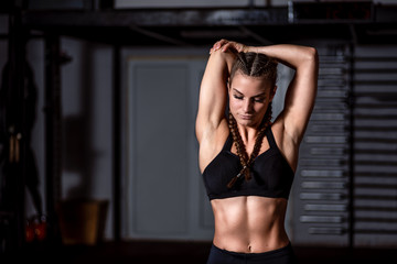 Young beautiful muscular attractive fit girl stretch her hand muscles after heavy hardcore cross...