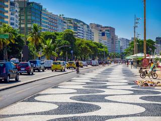 Fotobehang - Copacabana beach with palms and mosaic of sidewalk in Rio de Janeiro, Brazil. Copacabana beach is the most famous beach in Rio de Janeiro. Sunny cityscape of Rio de Janeiro