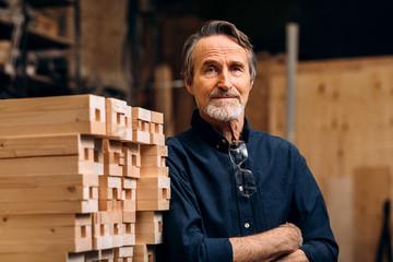Fototapeta Portrait of confident senior male carpenter standing in his workshop obraz