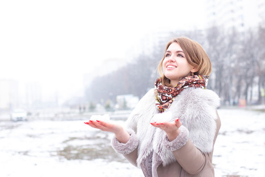 Happy young woman is playing with snow on a sunny winter day. Girl enjoys the winter, frosty day. Playing with snow in the winter holidays, a woman holds white loose snow in her hands.