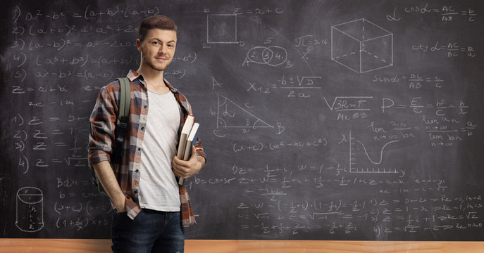 Male student posing in front of a blackboard with math formulas and equations