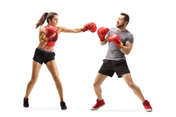 Young woman punching a man with boxing gloves