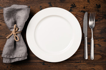 Table setting with empty white plate, cutlery and table napkin. Top view, copy space for text. Dinner table