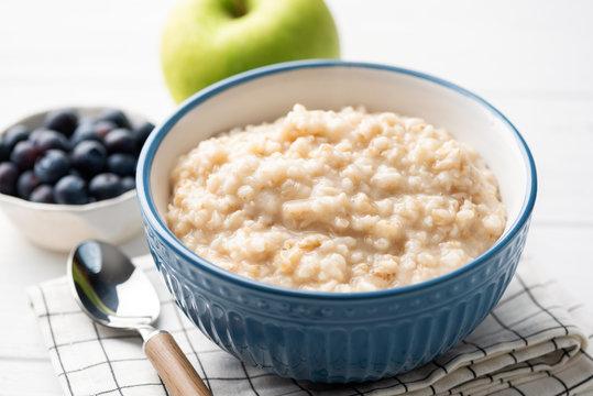 Healthy breakfast oatmeal porridge in bowl. Warm porridge oats, vegan vegetarian weight loss dieting breakfast food