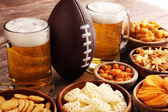 Chips, salty snacks, football and Beer on a table. Great for Bowl Game snack projects.