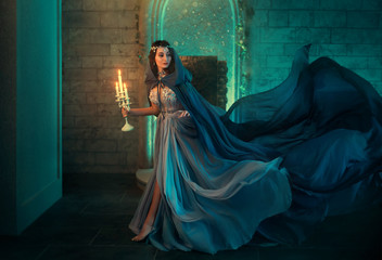 Fototapeta Luxury lady Queen medieval royal dress run escapes from Gothic night castle. Blue silk dress, cloak train plume waving motion. Holds in hands old candlestick burning candles. Background old retro room obraz