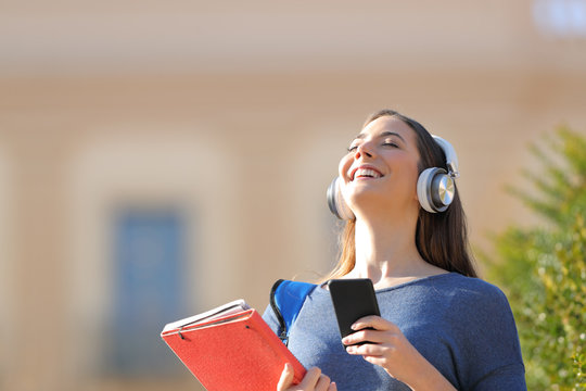 Happy student breathing fresh air listening to music