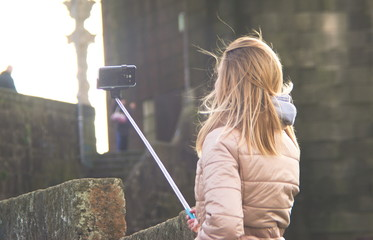 Menina a fazer uma selfie com um suporte de telemóvel