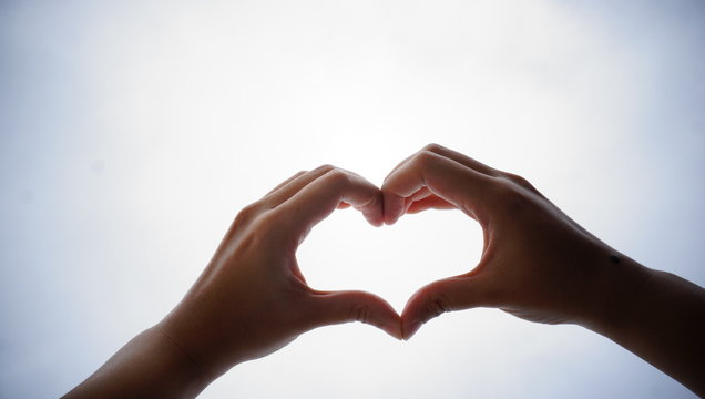 Close-Up Of Cropped Hands Making Heart Shape Against Clear Sky