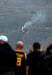 People watch as smoke rises from the scene of a helicopter crash that reportedly killed retired basketball star Kobe Bryant in Calabasas