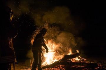 Fotobehang Kamperen People Standing By Bonfire Against Sky At Night