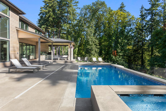 Luxury home exterior and pool on sunny day with blue sky