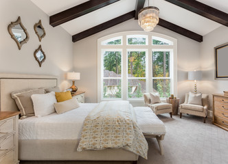 Beautiful furnished master bedroom interior in luxury home . Features vaulted ceiling with wood...