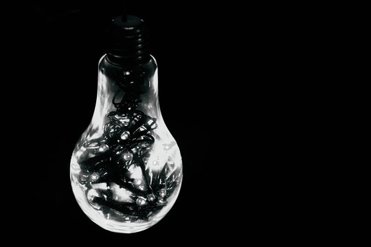 Close Up Of Light Bulb Hanging Against Black Background