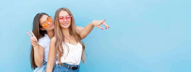 two young hipster woman friends in retro neon sunglasses standing and smiling over blue wall Wall mural