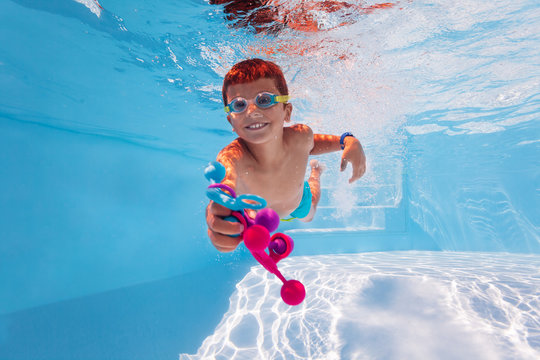 Cute happy boy swim underwater in the pool diving collecting colorful toys wearing googles