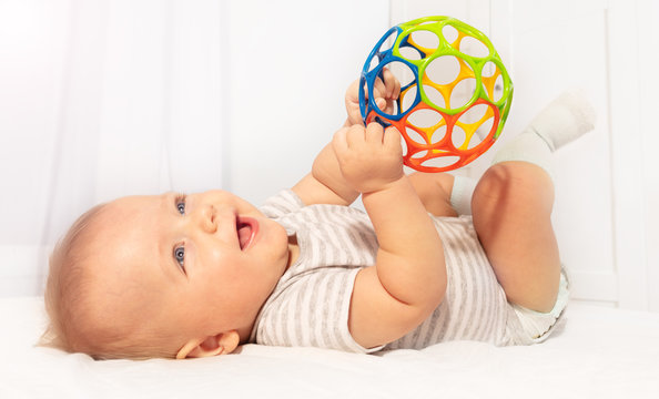 Little cute baby boy toddler play and hold toy ball laying on the back laughing