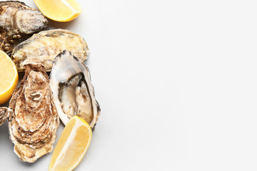 Tasty oysters with lemon on white background