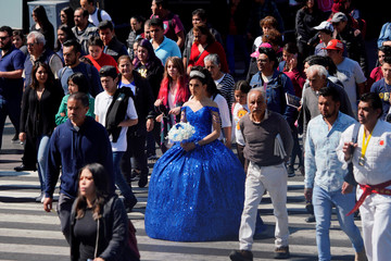 A girl wearing a quinceanera dress crosses the street during a photo session in Mexico City