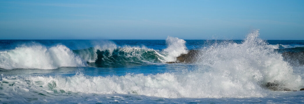 Large ocean waves crash against coastal stones on sunny day on European coast. Holidays, vacations on Atlantic ocean. High waves, surfing in Europe. Panoramic view. Tidal bore. Bay of Biscay, Spain.