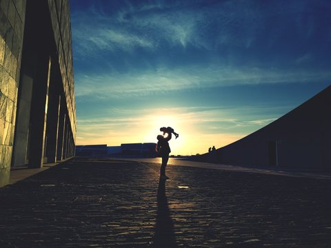 Mother Carrying Daughter While Standing On Road Against Sky During Sunset