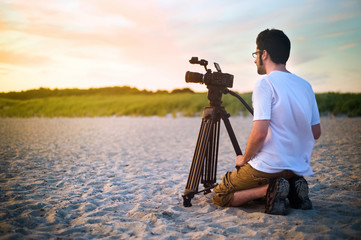 A young man shooting professional video outside on a beach