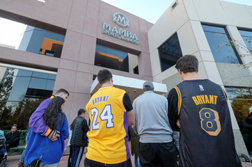 Fans gather at a makeshift memorial for former NBA player Kobe Bryant outside of the Mamba Sports Academy in Thousand Oaks