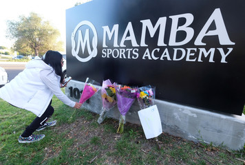 A fan places flowers at a makeshift memorial for former NBA player Kobe Bryant outside of the Mamba Sports Academy in Thousand Oaks