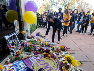 Fans place flowers at a makeshift memorial for former NBA player Kobe Bryant outside of the Mamba Sports Academy in Thousand Oaks