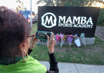 A fan takes pictures a makeshift memorial for former NBA player Kobe Bryant outside of the Mamba Sports Academy in Thousand Oaks