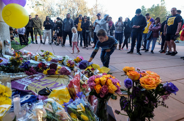 A young fan places a hat at a makeshift memorial for former NBA player Kobe Bryant outside of the Mamba Sports Academy in Thousand Oaks