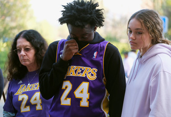 Fans react at a makeshift memorial for former NBA player Kobe Bryant outside of the Mamba Sports Academy in Thousand Oaks