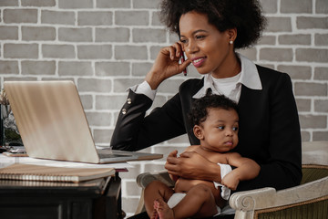 african american business woman taking care of her baby boy while working at home