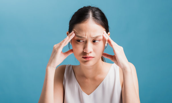 Asian beautiful women feeling confused and headache in blue color background.Concept of hard work without maintaining health and stress in the current environment