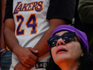 A mourner reacts while gathering with others in Microsoft Square near the Staples Center to pay respects to Kobe Bryant after a helicopter crash killed the retired basketball star, in Los Angeles