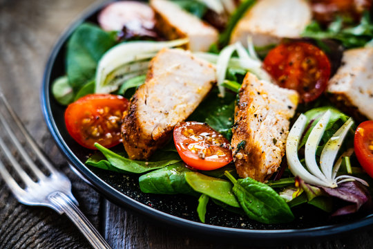 Caesar salad - barbecue chicken breast and vegetables on wooden table