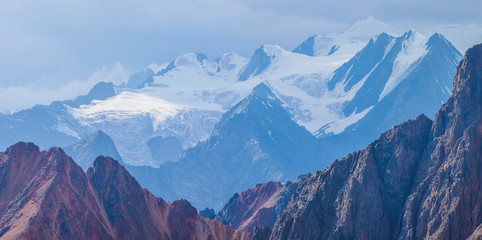 Wall Mural - Mountain view. Snow-capped peaks in a blue haze. Traveling in the mountains, trekking.