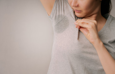 Attractive woman embarrassing on her sweat stain on her gray t-shirt.Asian female Nasty smell from sweat on her armpit with gray background.healthcare and hyperhidrosis or excessive sweating concepts