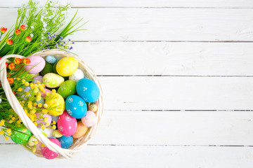 Colorful easter eggs in basket and flowers on white wooden table. Top view with copy space