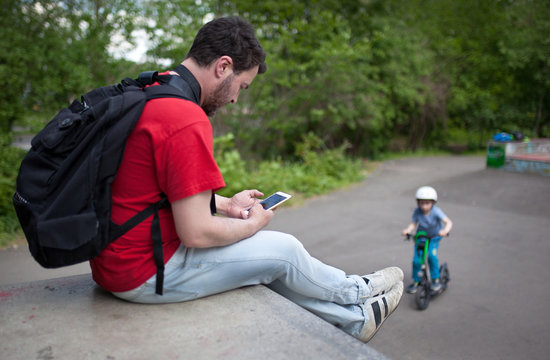 SIDE VIEW OF MAN USING MOBILE PHONE WHILE SITTING ON LEDGE