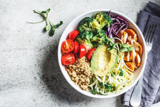Buddha bowl salad with quinoa, avocado, broccoli, sweet potato and tahini dressing, gray background.