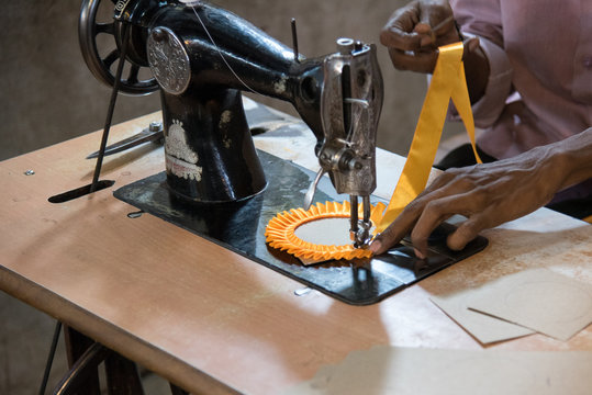 Midsection Of Tailor Using Sewing Machine While Stitching Textile