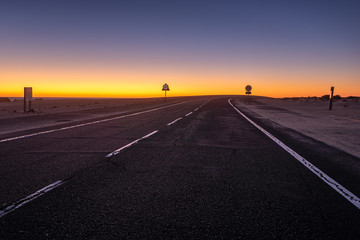 Aluminium Prints Night highway asphalt road running through the sandy desert at night