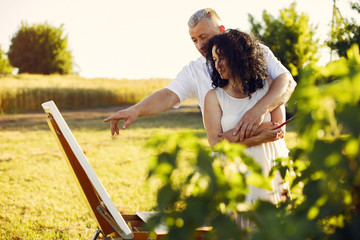 Woman artist painting with oil. Paints in a field. Adult couple spent time together