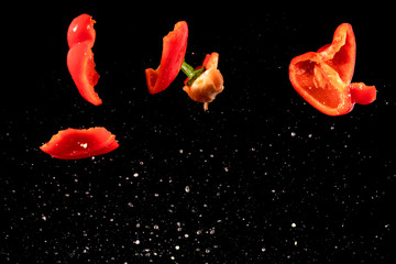 Slices of red peppers falling into the water